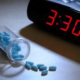 alarm clock that reads 3:30 and a bottle of split pills